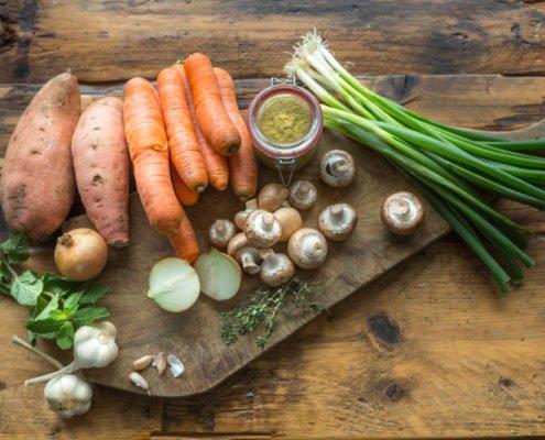 diverse groenten liggen op een houten ondergrond